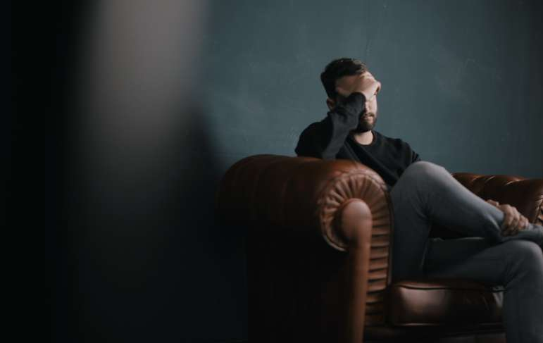 man sitting on couch with head in his hands